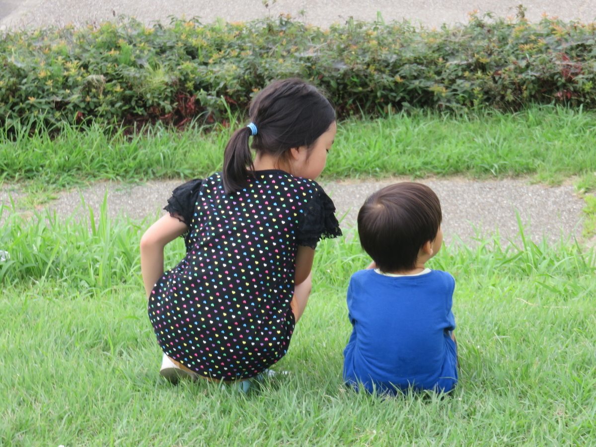 川岸に並んで座る姉と弟