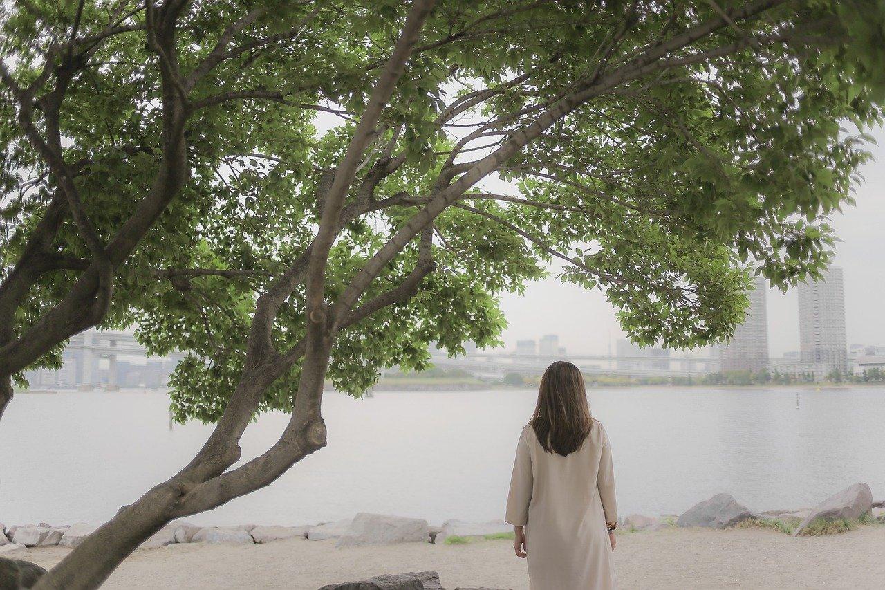 ビーチで一人たたずむ女性の後ろ姿